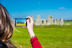 Taking a photo of Stonehenge. A young girl looking at the stones in Stonehenge and taking a photo with her smartphone Stock Photo
