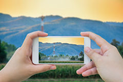 Taking photo of Telecommunication tower on the field Royalty Free Stock Images