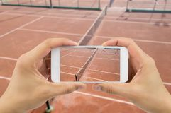 Taking photo at the tennis court. People taking a photo with the smartphone at the tennis match Royalty Free Stock Images