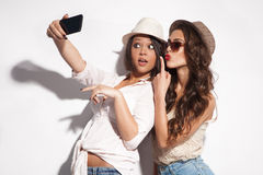 Taking photo. Two young women taking selfie with mobile phone Royalty Free Stock Image