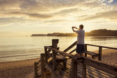 Taking photos of a beautiful sunset with a smartphone Royalty Free Stock Photography