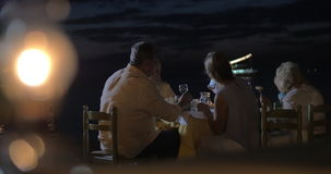 Taking photos during family dinner on the beach. Young woman taking picture of senior parents with mobile during late family dinner at the seaside. Defocused stock video footage