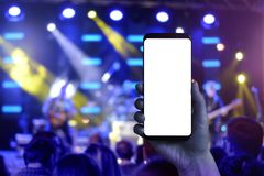 Taking photos of music concert with a mobile phone. Screen for mockup stock photos