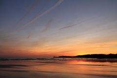 Taking photos of scenic view just before sunrise of silhouette deux jumeaux in colorful summer sky on a sandy beach Stock Photos