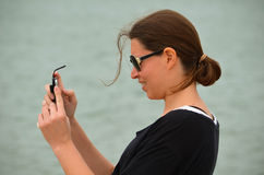 Taking Pics with Cell Phone. Side view of woman taking pictures on her cell phone in Matagorda, Texas stock photos