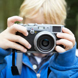 Taking a picture. Young child, taking a picture using a retro rangefinder camera royalty free stock photos