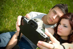Taking a picture. A young couple sit on the grass, attempting to take a picture of themselves Royalty Free Stock Photography