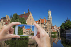 Taking picture of the Bruges (Belgium). In the bottom left of the photo are hands holding smart phone, whose screen contains color photo of the Rozenhoedkaail royalty free stock photos