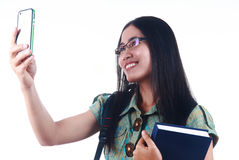 Taking picture with handphone. Woman student taking picture with her handphone isolated on white background Stock Photos