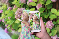 Taking picture with mobile phone of cute girl in nature Stock Photography