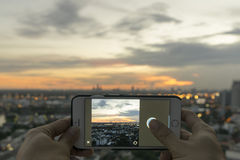 Taking Picture with Mobile Phone. Man is taking a picture of beautiful sunset from a rooftop with mobile phone Royalty Free Stock Photos