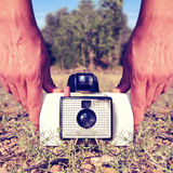 Taking a picture with an old instant camera. Closeup of a young man taking a picture with an old instant camera, placed on the ground, with a retro effect Royalty Free Stock Photography