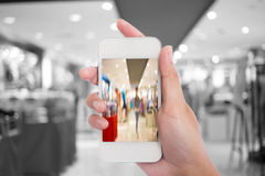 Taking a picture with a smart phone in shopping mall. Royalty Free Stock Photography