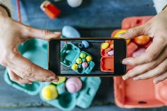 Taking a picture with the smartphone to Easter eggs. Stock Photos
