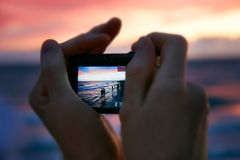 Taking picture at sunset. Focus on screen Royalty Free Stock Photos