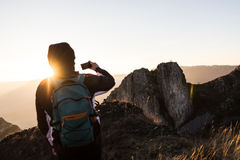 Young man taking a picture with his phone from the top of a mountain during the sunset Royalty Free Stock Photography
