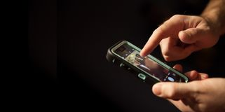 Taking a picture using a mobile phone. Operating or using a mobile phone camera app while in the dark Stock Images