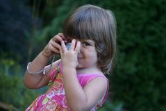 Taking pictures. A little girl playing with a digital camera Royalty Free Stock Photos