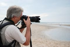 Taking pictures. Photographer  on the beach aiming his camera Stock Images