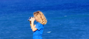 Taking pictures. Young blond girl with a camera taking pictures Royalty Free Stock Photo