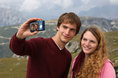 Taking pictures as holiday memory. Young couple taking pictures as a memory on the holiday royalty free stock photography