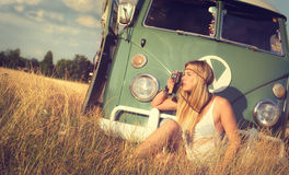 Taking pictures. Attractive blonde woman in front of an old caravan taking pictures Royalty Free Stock Images
