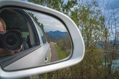 Taking pictures from the car. Photographer reflected in car mirror shooting pictures while driving through the beautiful green mountain valley stock photography