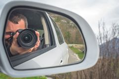Taking pictures from the car. Photographer reflected in car mirror shooting pictures while driving through the beautiful green mountain valley royalty free stock image