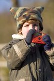 Taking Pictures in the Cold. A young boy wrapped up against the cold taking pictures royalty free stock image