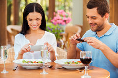 Taking pictures of food. Beautiful young loving couple taking pictures of their food and smiling while relaxing in outdoors restaurant together Stock Image