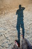 Taking pictures of his shadow on the beach royalty free stock photo