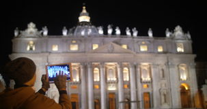 Taking pictures of night St. Peters Basilica. Illuminated St. Peters Basilica in Vatican City. Woman with tablet computer coming up and taking some pictures of stock footage