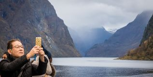 Taking pictures of norwegian fiords. Chinese or japanese tourist taking pictures of beautiful fjords on his mobile during Norway in a nutshell sightseeing tour royalty free stock photography