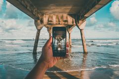 Taking pictures while in the sea under the jetty royalty free stock images