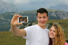 Taking pictures with a smartphone as holiday memory. Young couple taking pictures with a smartphone as a memory on the holiday royalty free stock image