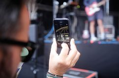 Taking pictures using smartphone during music festival. A man uses his smartphone to take pictures during a music live show at Sonar advanced music and arts in Royalty Free Stock Photos