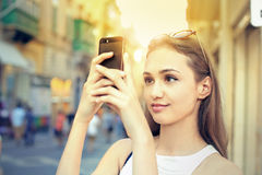 Taking pictures. Young woman taking pictures in the city Royalty Free Stock Photos