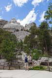 Taking a Picure of Mount Rushmore. A young man stands by a railing at the base of the mountain to take a picture of Mount Rushmore with pine trees and blue sky royalty free stock photos