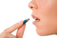Taking pill. Profile of young woman holding pill by her mouth before taking it Stock Photo