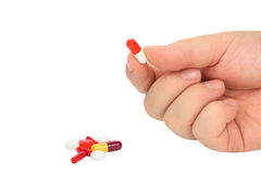 Taking a pill. Male hand picking a pill on pure white background Stock Images