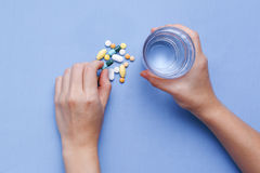 Taking pill with hand holding glass of water Stock Photo