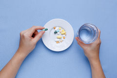 Taking pill with pills on plate Royalty Free Stock Photos