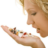 Taking pills. Blonde woman holding a heap of pills in her palm stock photography