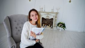 Girl Student Posing With Papers and Folders, Smiling, and Sitting in Chair. Taking Portrait Pretty Girl. Women Smiling and Looking Into Lens of Photographer Royalty Free Stock Photography