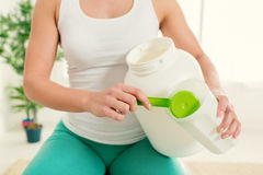 Taking Protein Supplements. Close-up of a fitness woman pouring Nutritional protein Supplements into shaker Royalty Free Stock Image