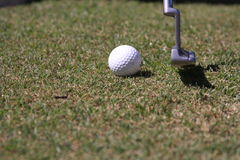 Taking a putt at golf. ( close up of putter and golf ball Royalty Free Stock Image