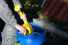 Taking rainwater with watering can Stock Image
