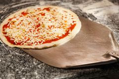 Taking raw pizza with metal shovel for baking Royalty Free Stock Photography