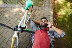 Taking Rest from Cycling. High angle view of cheerful Indian man talking to friend on smartphone while taking rest from cycling, he lying on park bench while Stock Image