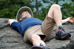 Taking a Rest. A man lies on a rock and takes a nap during a hike Royalty Free Stock Photo